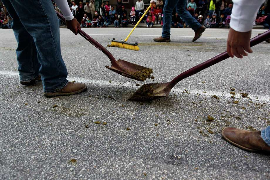 The Texas A&M Parsons Mounted Cavalry clean up their mess as they followed their horses during the 2013 Downtown Rodeo Parade Saturday, Feb. 23, 2013, in Houston. Photo: Johnny Hanson, Houston Chronicle / © 2013  Houston Chronicle