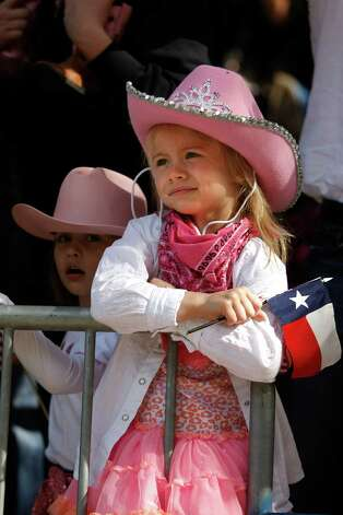 Ava Ramsower, 5, right, holds a Texas flag and she and her cousin Treasa Rice, 4, left, watched the 2013 Downtown Rodeo Parade Saturday, Feb. 23, 2013, in Houston. Photo: Johnny Hanson, Houston Chronicle / © 2013  Houston Chronicle