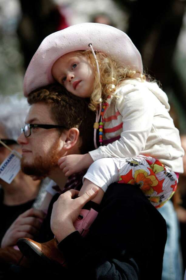 Alice Watson, 3, gets comfortable on her father, Jonathan, Watson as they watched the 2013 Downtown Rodeo Parade Saturday, Feb. 23, 2013, in Houston. Photo: Johnny Hanson, Houston Chronicle / © 2013  Houston Chronicle