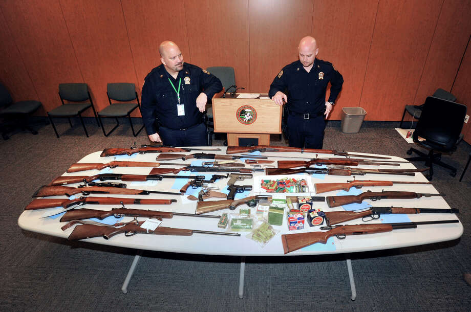 Greenwich Police Detective, Anthony Fiscella, left, and Greenwich Police Officer, Keith Hirsch, display weapons turned in to the police during the Weapons Turn In program held at Greenwich Police Headquarters, Saturday, Feb. 23, 2013. The weapons included 14 long guns, 3 pistols, 3 BB pistols, 3 BB rifles, 2 BB pistols, 5 knives, 1 sword and 1 spear. Photo: Bob Luckey / Greenwich Time