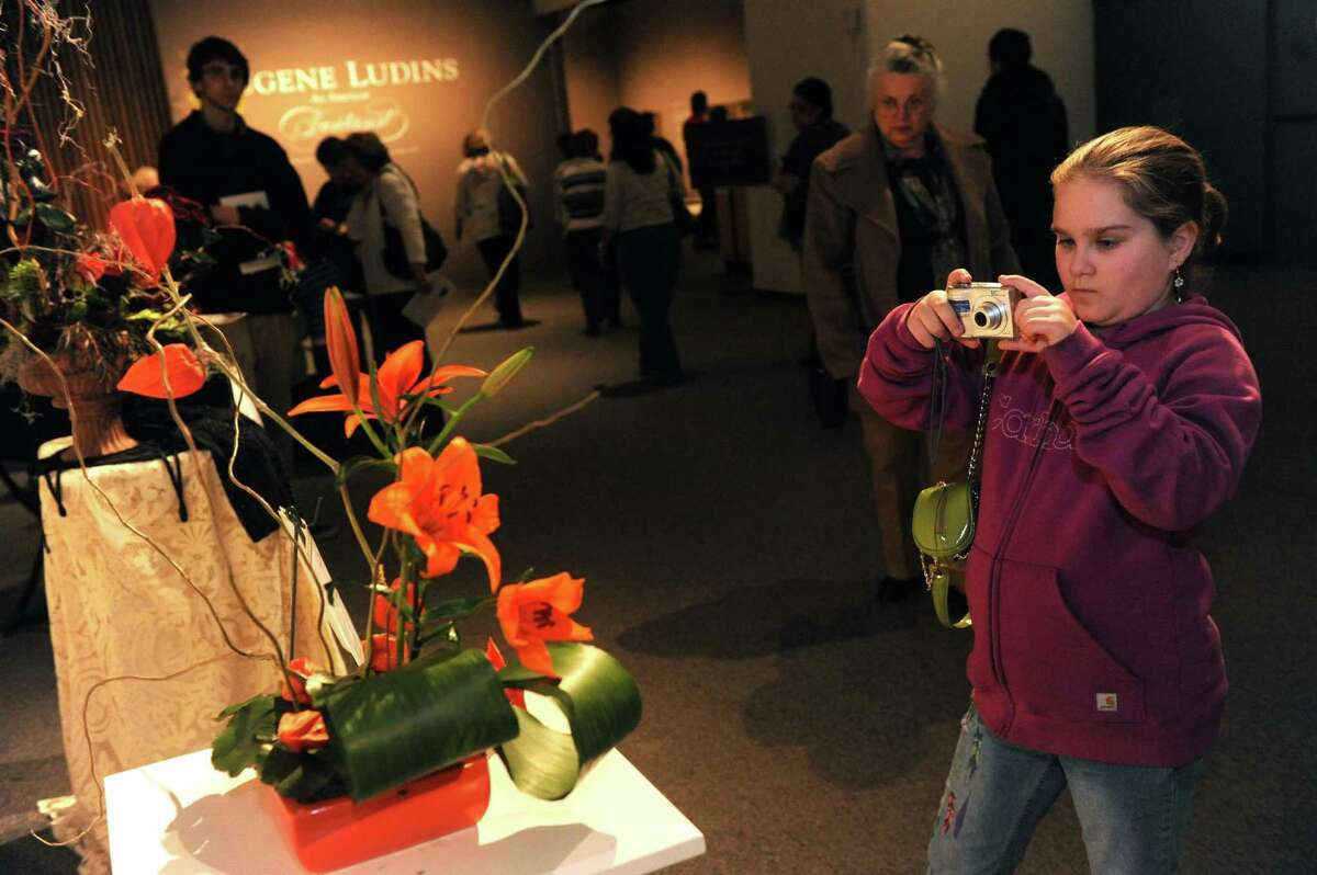 Ten-year-old Sophia VanDerwarker photographs a floral design by Pamela Love of the Van Rensselaer Garden Club during the 22nd Annual New York in Bloom at the New York State Museum on Saturday Feb. 23, 2013 in Albany, N.Y. (Michael P. Farrell/Times Union)