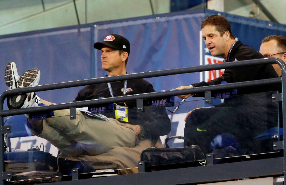 Brothers Jim and John Harbaugh watch players from the stands at the NFL scouting combine. Photo: Dave Martin