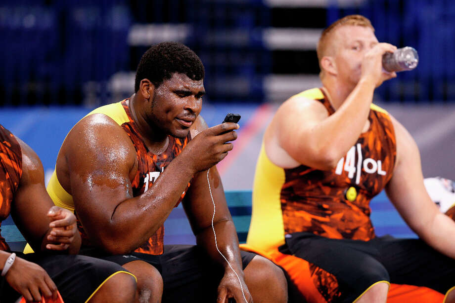 D.J. Fluker of Alabama looks at his phone following a workout during the combine. Photo: Joe Robbins / 2013 Getty Images