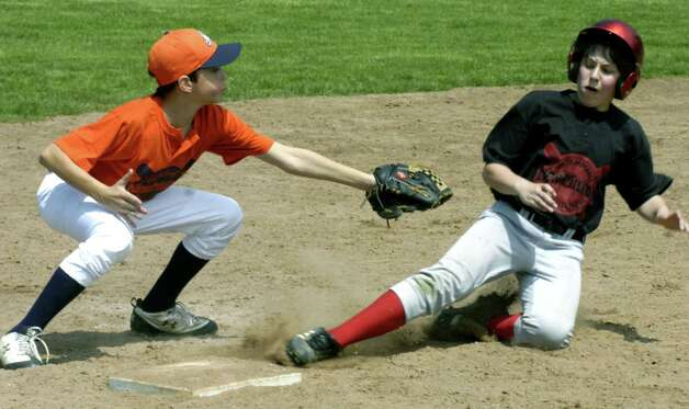 Third baseman Trevor Halas  of the Howland &  Associates' Cal State Fullerton Titans reaches out to tag Cal Martin of the Food & Ankle Specialists Georgia Bulldogs in a bang-bang early-season play May 1, 2010 in New Milford Youth Baseball/Softball 'AAA' baseball at Garick Farms fields. Photo: Norm Cummings