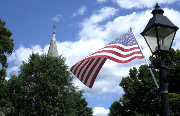 The American flag flies in a gentle summer's breeze from a lamppost along Main Street in New Milford. The steeple of St. John's Episcopal Church emerges above the treetops across the Village Green. July 14, 2009 Photo: Norm Cummings