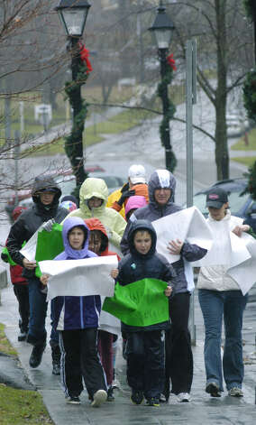 Five New Milford mothers and their children followed Friday morning's moment of silence and bell ringing dedicated to those who died Dec. 14, 2012 in Newtown by walking slowly through the rain and blustery wind around the Village Green in New Milford, each carrying a poster bearing the name of one of those who died. Among the participants are, front left, Paige Tannone, Hannah Ciampini, behind Paige, and Landon Tannone. Among the moms are, from left to right, Aimee Ciampini, Kayla Tannone, Mary Kate Tannone and Rebecca Chepren. Also lending their efforts to the demontration are Starr Gustas, Skylar Gustas, Luke Gustas, Jessica Stellato, Kyleigh Stelatto, Braydon Stellato and Lauren Tannone. Paige and Landon Tannone are carrying respective posters honoring Sandy Hook Elementary School principal Dawn Hochsprung and teacher Lauren Rousseau. Photo: Norm Cummings