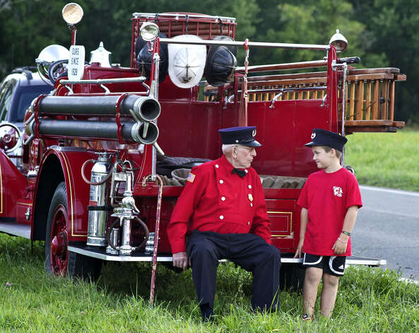 William Newton, a veteran of the Kent Volunteer Fire Deparment, shares a special moment with great-grandson William Star during the Kent Firemen's Fair in August 2011. Then event was among the highlights of a special year for the Kent firefighters, who celebrated their 100th year of service to the community. Photo: Trish Haldin