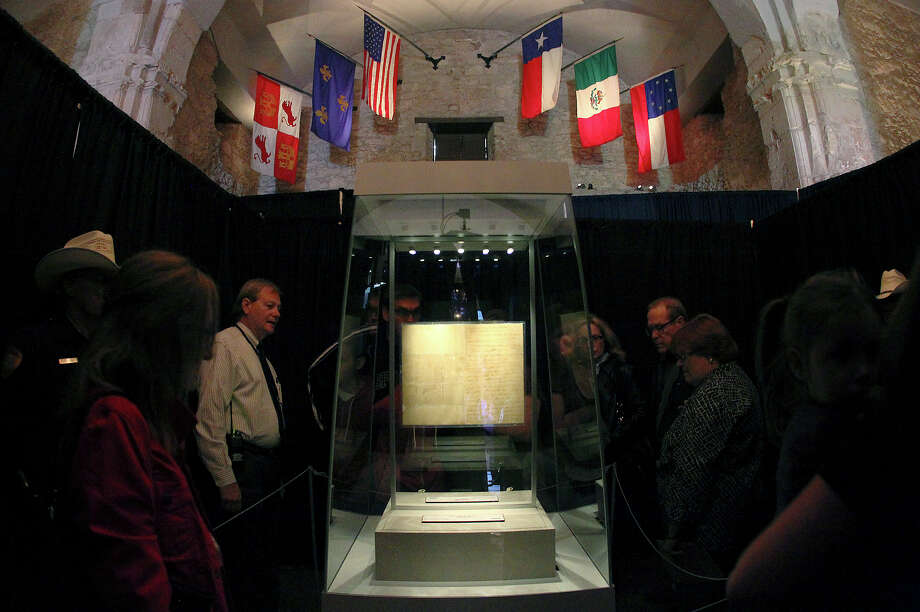 "John Anderson (third from left) from the Texas State Library and Archives points out facts about the letter written by William Barret Travis to visitors at the Alamo on Saturday, Feb. 23, 2012. Visitors stood in line for nearly two hours to get a glimpse of the original ""victory or death"" letter written by Travis on the first day of the exhibit. Officials are anticipating at least twice the amount of traffic than usual at the Texas Shrine. The letter will be on display at the Alamo through March 7th to commemorate the 177th anniversary of the battle at the Alamo. Photo: Kin Man Hui, San Antonio Express-News / © 2012 San Antonio Express-News"