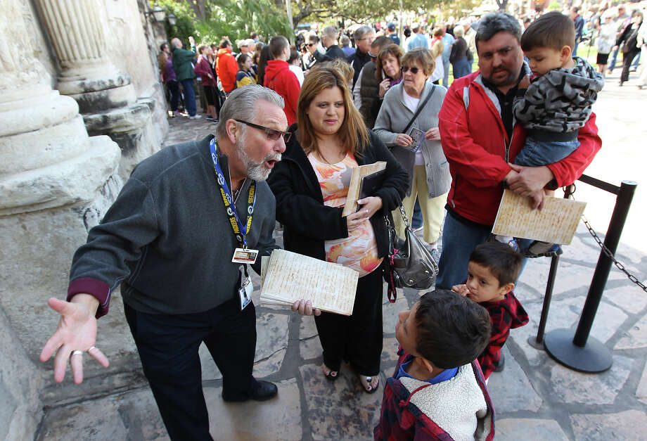 "Volunteer docent Don Townsend (left) chats up Vanessa  and Jose Soto's children while they wait to go into the Alamo and get a glimpse of the letter written by William Barret Travis to visitors at the Alamo on Saturday, Feb. 23, 2012. Vanessa said she was a fourth-grade social studies teacher and wanted to bring her kids to see the historical document. Visitors stood in line for nearly two hours to get a glimpse of the original ""victory or death"" letter written by Travis on the first day of the exhibit. Officials are anticipating at least twice the amount of traffic than usual at the Texas Shrine. The letter will be on display at the Alamo through March 7th to commemorate the 177th anniversary of the battle at the Alamo. Photo: Kin Man Hui, San Antonio Express-News / © 2012 San Antonio Express-News"