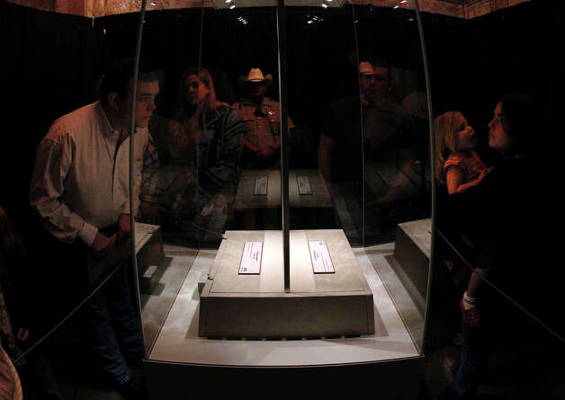 "Visitors catch a glimpse of the original historic letter written by William Barret Travis contained in an archival display in the Alamo on Saturday, Feb. 23, 2012. Visitors stood in line for nearly two hours to see the ""victory or death"" letter written by Travis on the first day of the exhibit. Officials are anticipating at least twice the amount of traffic than usual at the Texas Shrine. The letter will be on display at the Alamo through March 7th to commemorate the 177th anniversary of the battle at the Alamo. Photo: Kin Man Hui, San Antonio Express-News / © 2012 San Antonio Express-News"