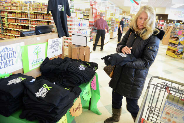 "Natalie Jodan, of Sandy Hook, Conn., picks up ""We Are Newtown"" T-shirts for her friends at Big Y World Class Market in Newtown, Conn. on Thursday, Feb. 21, 2013. It has been more than two months since 20 students and six staff members were killed at Sandy Hook Elementary School and the community is still recovering. Photo: Tyler Sizemore / The News-Times"