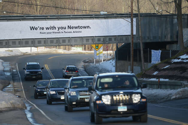"Cars drive under a ""We're with you Newtown"" sign in Newtown, Conn. on Thursday, Feb. 21, 2013.  It has been more than two months since 20 students and six staff members were killed at Sandy Hook Elementary School and the community is still recovering. Photo: Tyler Sizemore / The News-Times"