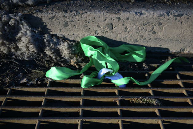 A discarded Sandy Hook commemorative ribbon lies in a gutter in Sandy Hook, Conn. on Thursday, Feb. 21, 2013.  It has been more than two months since 20 students and six staff members were killed at Sandy Hook Elementary School and the community is still recovering. Photo: Tyler Sizemore / The News-Times