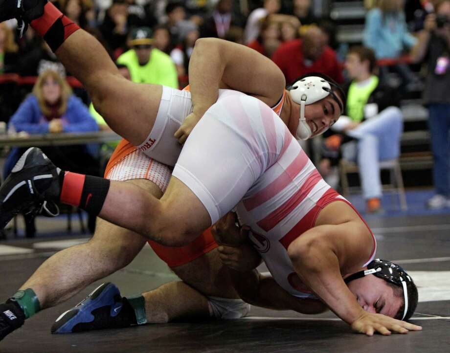 Ivan DeLeon of Katy Seven Lakes drives Alfonso Kaihua of Euless Trinity into the mat during the 285 lb. class final. Photo: Erich Schlegel, Houston Chronicle / ©2013 Erich Schlegel