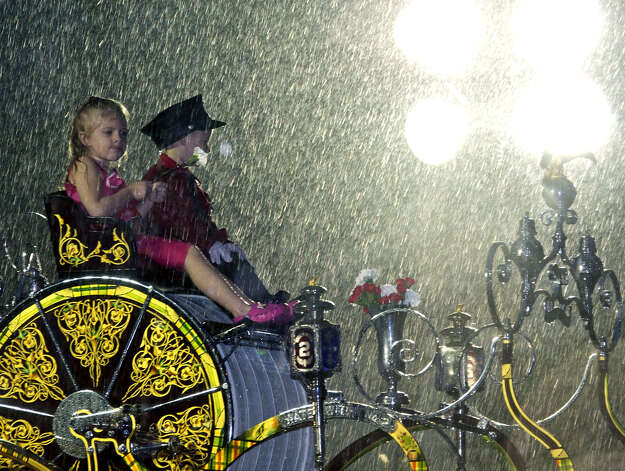 A pair of very wet but quite contented youngsters enjoy their ride aboard Witch Hose Co. No. 2 firefighters' ceremonial carriage as they cruise Main Street (Route 133) during the opening parade for the Bridgewater Country Fair in August 2011. Photo: Trish Haldin