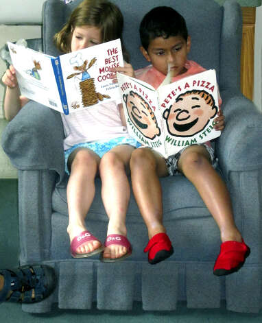Students buddy up to share a chair while reading at the Children's Center of New Milford in August 2011 Photo: Norm Cummings