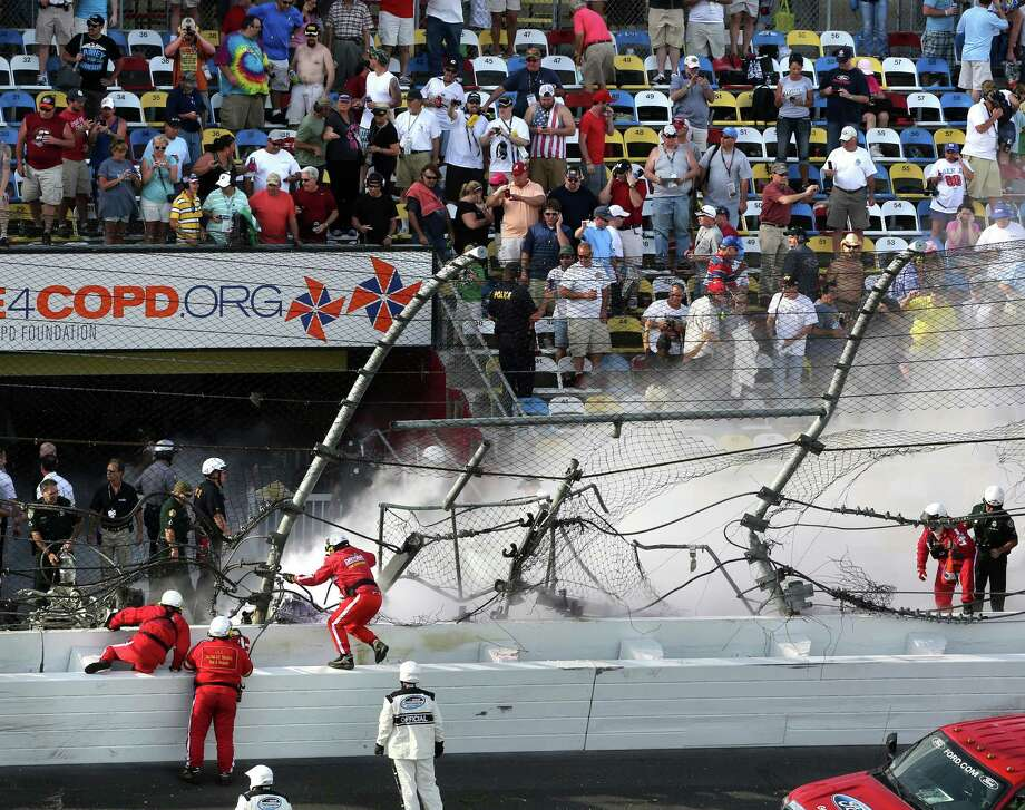 Emergency personnel climb the safety wall to get the burning wreckage that destroyed the catch-fence at the finish line in the final seconds of the Nationwide 300 race at Daytona International Speedway in Daytona, Beach, Florida Saturday, February 23, 2013. Photo: Joe Burbank, McClatchy-Tribune News Service / Orlando Sentinel
