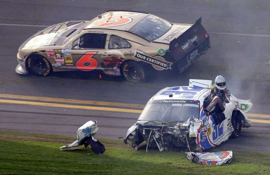 Driver Kyle Larson climbs out of his car as Trevor Bayne (7) rolls past after a crash at the conclusion of the NASCAR Nationwide Series auto race Saturday, Feb. 23, 2013, at Daytona International Speedway in Daytona Beach, Fla. Photo: Chris O'Meara, Associated Press / AP