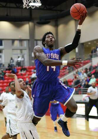 West Brook?s Michael Zeno, No. 14, attempts a layup during the Class 5A playoff game against Clear Brook Friday in the Lee College Sports Arena and Wellness Center in Baytown, TX. (Matt Billiot / Special to the Enterprise)