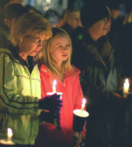 "Peggy Remlin and her daughter, Tiffany, 12, of New Milford join the singing of ""Silent Night"" during the vigil on the New Milford Village Green in remembrance of Dec. 14, 2012 tragic shootings in Newtown. Photo: Trish Haldin"