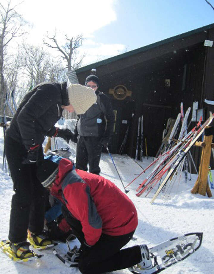 Cross country experts help beginners mount their snowshoes Thursday, Feb. 21 , 2013, at the Garnet Hill Cross County Ski Center in North River, N.Y. (Rick Karlin/Times Union) Photo: Tutu