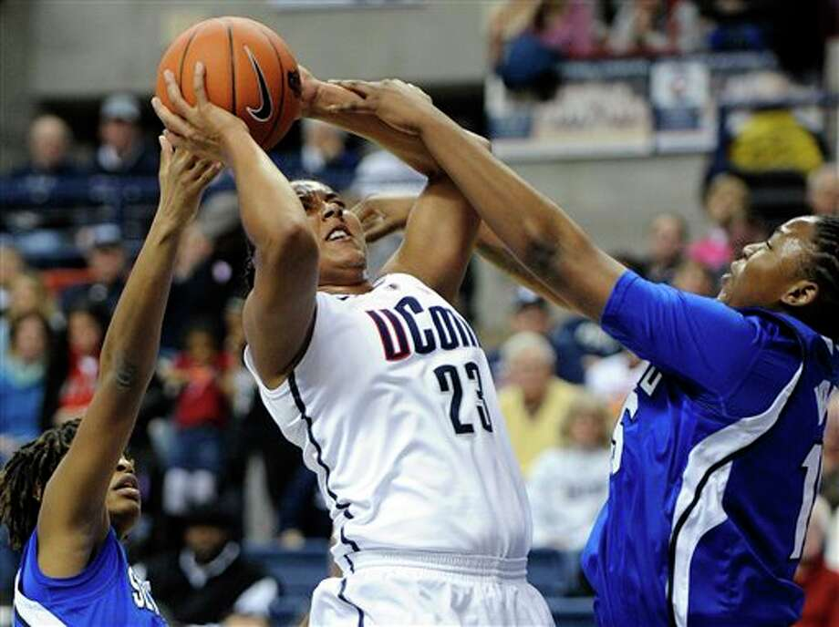 Connecticut's Kaleena Mosqueda-Lewis, center, is fouled by Seton Hall's Brittany Webb, right, as Tabatha Richardson-Smith looks on during the first half of an NCAA college basketball game in Storrs, Conn., Saturday, Feb. 23, 2013. Mosqueda-Lewis scored her thousandth point during the half. (AP Photo/Fred Beckham)