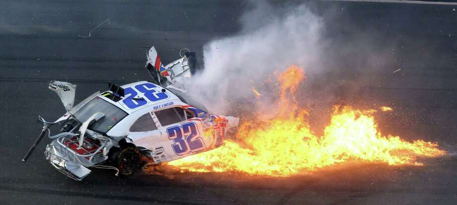 Flames burn from the the car of Kyle Larson (32), after he crashed into the catch fench at the finish line in the final seconds of the Nationwide 300 race at Daytona International Speedway in Daytona Beach, Florida, Saturday, February 23, 2013. Photo: Joe Burbank, McClatchy-Tribune News Service / Orlando Sentinel