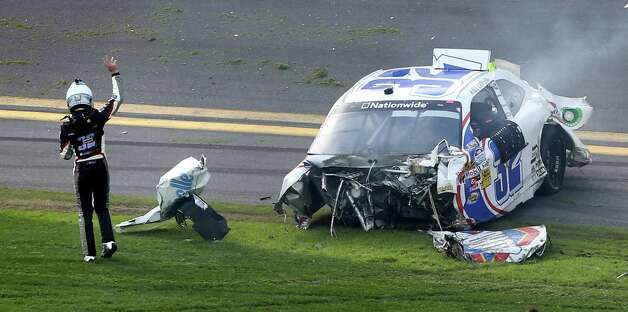 Driver Kyle Larson waves to indicate he is okay after crashing into the catch fench at the finish line in the final seconds of the Nationwide 300 race at Daytona International Speedway in Daytona Beach, Florida, Saturday, February 23, 2013. Photo: Joe Burbank, McClatchy-Tribune News Service / Orlando Sentinel