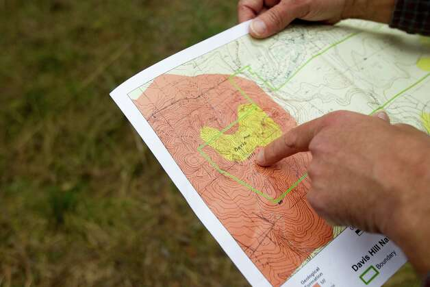 Andrew Sipocz looks at a topographical map while hiking at Davis Hill Natural Area Wednesday, Feb. 20, 2013, near Tarkington, Texas. The tract of land was purchased by Texas Parks and Wildlife in 1983, but has never been developed to be used by the public. Photo: Brett Coomer, Houston Chronicle / © 2013 Houston Chronicle
