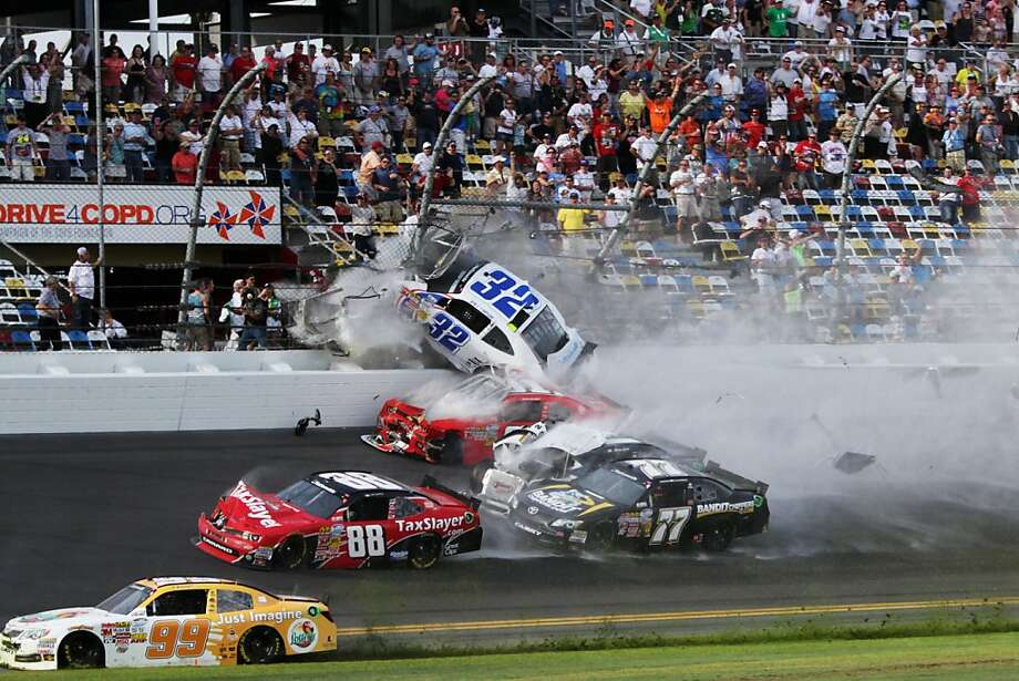 Kyle Larson's car (32) goes airborne after a last-lap crash; large chunks of debris from his car injured fans. Photo: Jerry Markland, Getty Images