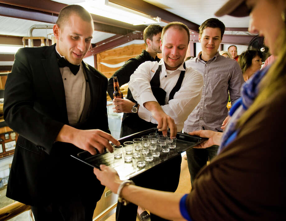 """Matt Jelinski, left, of Dallas, and Davis Pullig, center, of San Antonio take samples of """"white dog,"""" distilled bourbon before it's been aged in a barrel, from hospitality assistant Jan Gignac, right, during a tour at Garrison Bros. Distillery in Hye, TX on Sat., Jan 12, 2013.  Jelinski and Pullig wore tuxedoes to the tour just for fun. Photo: Ashley Landis, For The Houston Chronicle / copyright 2013 Ashley Landis"""