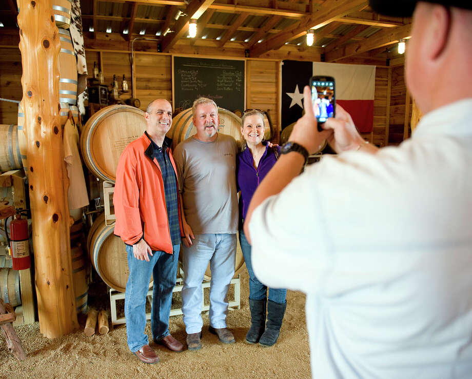 Visitors Scott, left, and Mary Altorfer, right, of Katy, TX have their photo taken with distillery owner Dan Garrison, center, by chauffer Scott Garner, right, of Dripping Springs at Garrison Bros. Distillery in Hye, TX on Sat., Jan 12, 2013. Photo: Ashley Landis, For The Houston Chronicle / copyright 2013 Ashley Landis