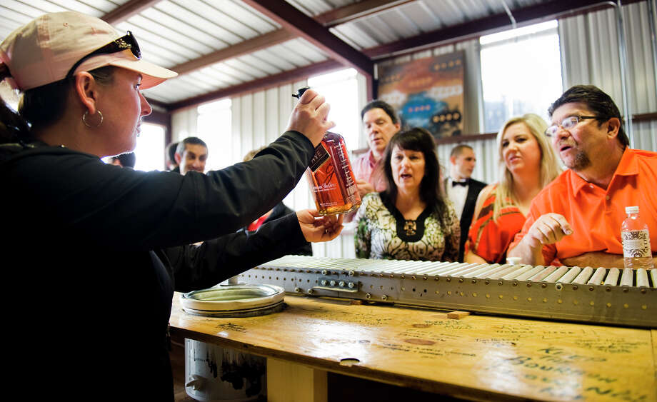 Hospitality manager Stephanie Whitworth, left, shows off the signature of Dan Garrison to a tour group in the bottling room at Garrison Bros. Distillery in Hye, TX on Sat., Jan 12, 2013.  Garrison, the distillery owner, signs and numbers every bottle by hand. Photo: Ashley Landis, For The Houston Chronicle / copyright 2013 Ashley Landis