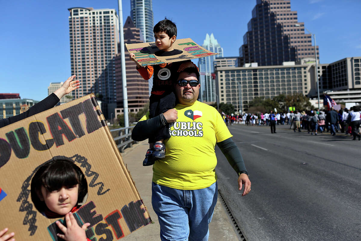 Noel Candelaria, Vice President of the Texas State Teacher Association, walks with his family including his son, Patrick, 3, and daughter, Noel, 6, left, on the Congress Ave. bridge to join the Save Texas Schools March to the Texas State Capitol for a rally in Austin on Saturday, Feb. 23, 2013.