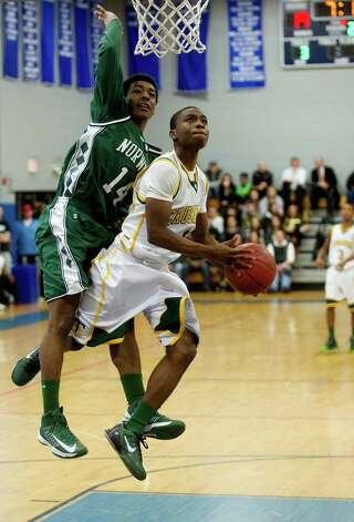 Trinity Catholic's Shadrac Casimir takes a shot as he is defended by Norwalk's Jabari Dear during Saturday's FCIAC quarterfinal game at Fairfield Ludlowe High school on February 23, 2013. Photo: Lindsay Perry / Stamford Advocate