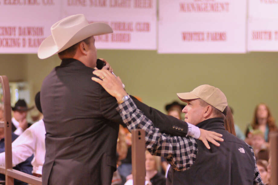 San Antonio Stock Show and Rodeo auctioneer C. Jason Spence (left) and Buddy Long embrace prior to the annual auction as Spence talked about Long's son, Kollin, who has been a regular auction participant and was recently killed by lightning. Photo: Robin Jerstad, Robin Jerstad / For The Express-News
