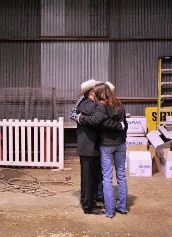 Auctioneer C. Jason Spencer (left) hugs Buddy and Theresa Long after talking about the Long's son, Kollin, a regular rodeo auction participant who was recently killed by lightning. Photo: Robin Jerstad, Robin Jerstad / For The Express-News