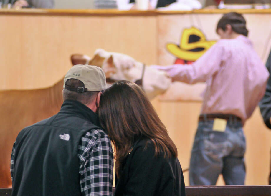 Buddy and Theresa Long embrace as their son Karter holds his champion hereford and their late son, Kollin, is remembered by those at the San Antonio Stock Show and Rodeo Saturday. Kollin was recently killed after being stuck by lightning. Photo: Robin Jerstad, Robin Jerstad / For The Express-News