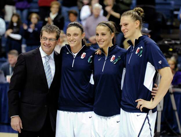 Geno Auriemma, Kelly Faris, Caroline Doty, and Heather Buck, left to right, receive awards during Senior Night ceremonies before Connecticut's NCAA basketball game against Seton Hall in Storrs, Conn., Saturday, Feb. 23, 2013. (AP Photo/Fred Beckham) Photo: Fred Beckham, Associated Press / FR153656 AP
