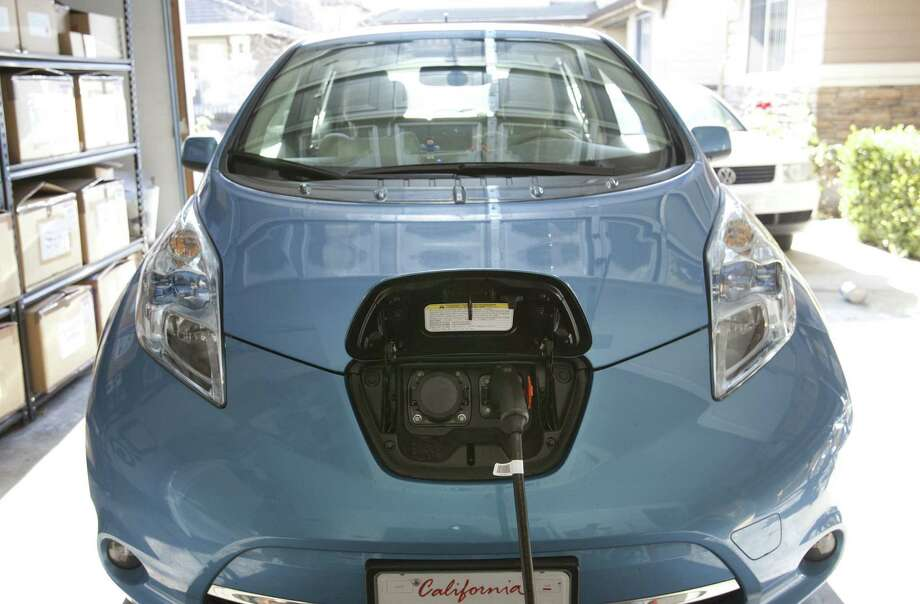 A Nissan Leaf is plugged into an electric vehicle charger in Fremont, Calif. Sales of the Leaf and other electric vehicles have fallen short of expectations, leading some analysts to call the EV's a niche product. Photo: McClatchy-Tribune News Service