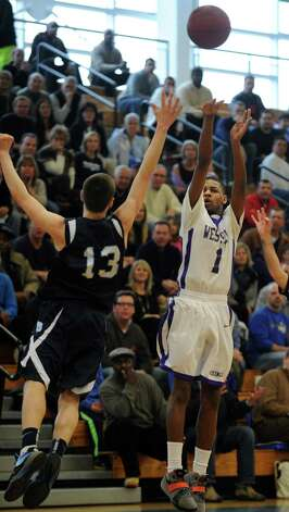 Westhill's Jeremiah Livingston puts up the ball as Wilton's Matt Shifrin defends during the FCIAC boys' basketball quarterfinals Saturday, Feb. 23, 2013 at Fairfield Ludlowe High School in Fairfield, Conn. Photo: Autumn Driscoll / Connecticut Post