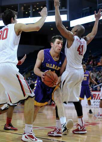 Albany's Sam Rowley drives to the net as Fairfield's Josip Mikulic, left, and Keith Matthews guard him Saturday, Feb. 23, 2013 at the Webster Bank Arena in Bridgeport, Conn. Photo: Autumn Driscoll / Connecticut Post