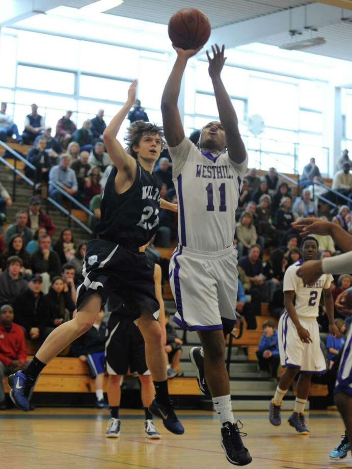 Westhill's Guyveson Cassamajor puts up the ball as Wilton's Chris Curtis defends during the FCIAC boys' basketball quarterfinals Saturday, Feb. 23, 2013 at Fairfield Ludlowe High School in Fairfield, Conn. Photo: Autumn Driscoll / Connecticut Post