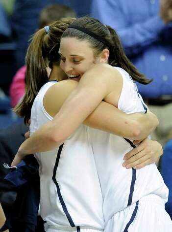 Connecticut's Kelly Faris hugs teammate Caroline Doty after scoring her 1000th career point during the second half of Connecticut's 90-30 victory over Seton Hall in an NCAA college basketball game in Storrs, Conn., Saturday, Feb. 23, 2013. Faris scored a game-high 18 points in the win. (AP Photo/Fred Beckham) Photo: Fred Beckham, Associated Press / Associated Press