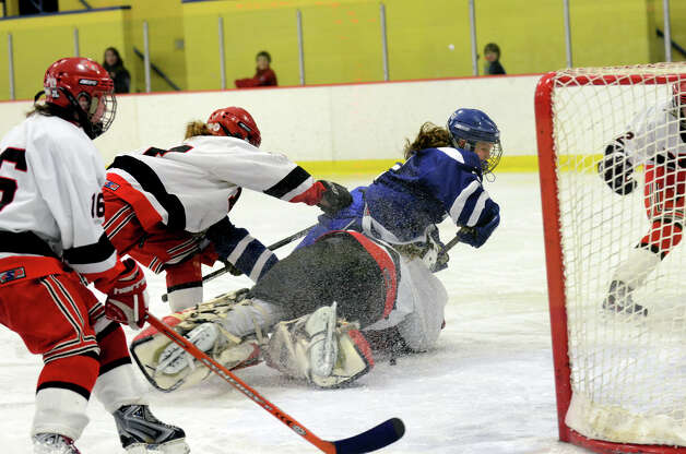 Darien's Georgia Cassidy (2) falls into New Canaan's goalie Nathalie Deney (1) as the puck slides into the goal securing Darien's 4-3 win over New Canaan in the third period during the FCIAC girls hockey finals at Terry Conners Rink in Stamford on Saturday, Feb. 23, 2013. Photo: Amy Mortensen / Connecticut Post Freelance