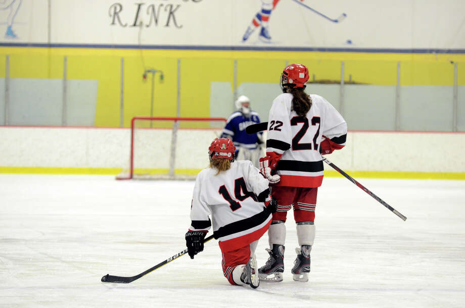 New Canaan's Madzie Carroll (14) and Olivia Hompe (22) react after Darien wins the FCIAC girls hockey finals at Terry Conners Rink in Stamford on Saturday, Feb. 23, 2013. Photo: Amy Mortensen / Connecticut Post Freelance