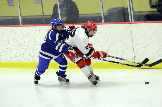 Darien's Sage Thacher (13) defends against New Canaan's Olivia Hompe (22) during the FCIAC girls hockey finals at Terry Conners Rink in Stamford on Saturday, Feb. 23, 2013. Photo: Amy Mortensen / Connecticut Post Freelance