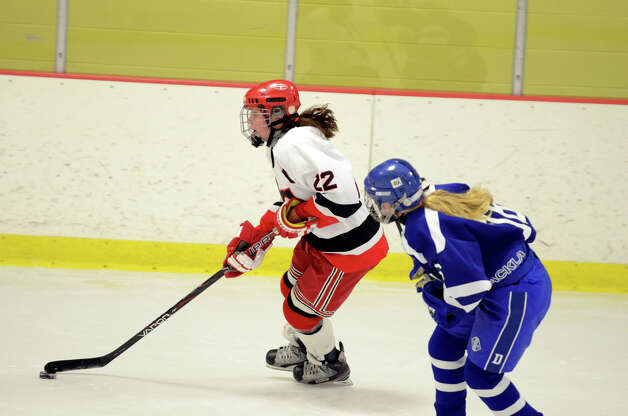 New Canaan's Oliva Hompe (22) controls the puck during the FCIAC girls hockey finals against Darien at Terry Conners Rink in Stamford on Saturday, Feb. 23, 2013. Photo: Amy Mortensen / Connecticut Post Freelance