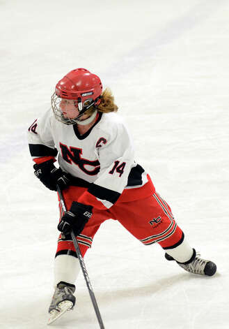 New Canaan's Madzie Carroll (14) controls the puck during the FCIAC girls hockey finals against Darien at Terry Conners Rink in Stamford on Saturday, Feb. 23, 2013. Photo: Amy Mortensen / Connecticut Post Freelance