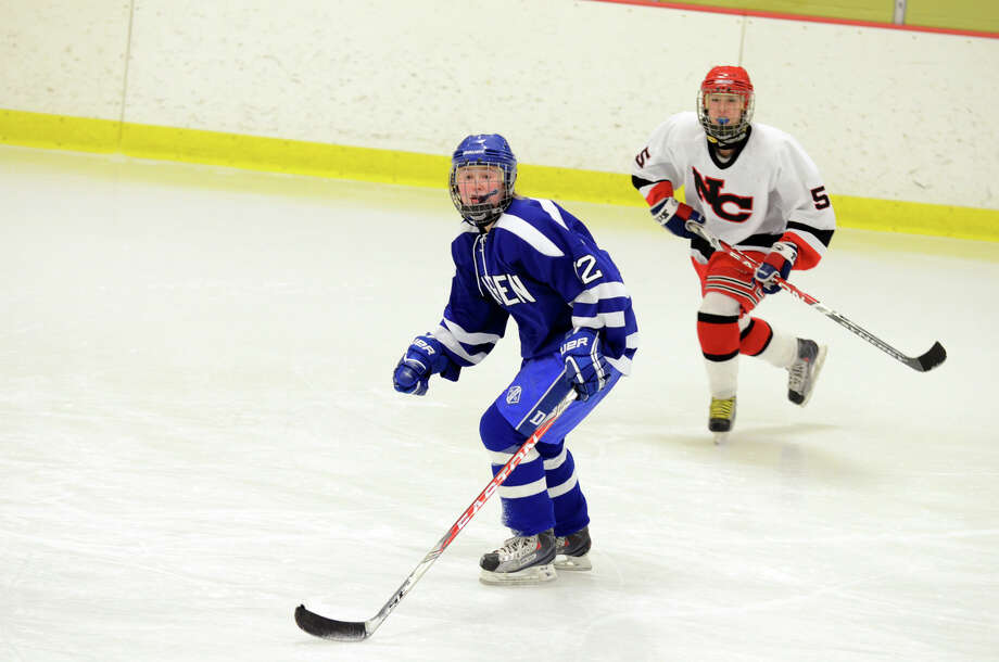 Darien's Amanda Sload (12) and New Canaan's Emma Rosnstein (5) on the ice during the FCIAC girls hockey finals at Terry Conners Rink in Stamford on Saturday, Feb. 23, 2013. Photo: Amy Mortensen / Connecticut Post Freelance